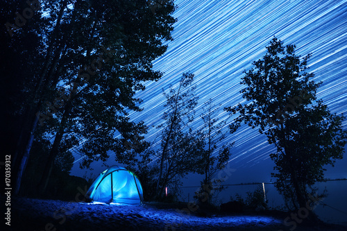 Tent set among the trees on coast of a river with star trails in the night sky