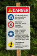 A danger sign with various beach rules on it