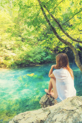 Young woman sitting near the beautiful lake in nature.