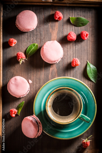 Poster Delicious pink macaroons served with hot coffee