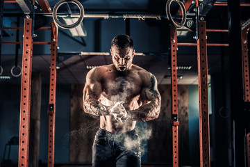 Strong muscular man preparing for workout in crossfit gym. Workout lifestyle concept. Young athlete practicing crossfit training