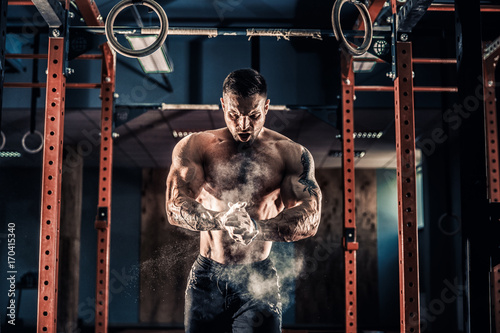 Sticker Strong muscular man preparing for workout in crossfit gym. Workout lifestyle concept. Young athlete practicing crossfit training