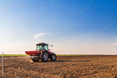 Plakát Farmer fertilizing arable land with nitrogen, phosphorus, potassium fertilizer