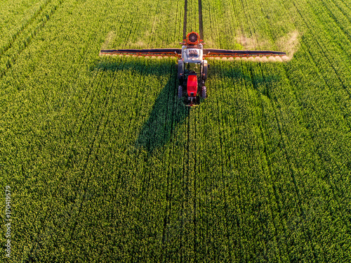 Farmer spraying green wheat field Poster