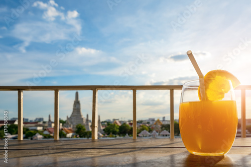 Fotobehang Bangkok Holidays Concept, Fruit refreshment on wooden terrace foreground and Wat Arun Bangkok Landmark background, Wat Arun riverside Bangkok, Thailand.
