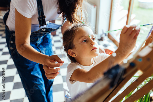 Happy family. Mother and daughter dressed in white shirt and blue jeans together paint. Adult woman helps the child girl. New housing, art and family leisure concept.