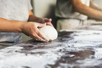 Baker preparing bread. Close up of hands kneading dough.