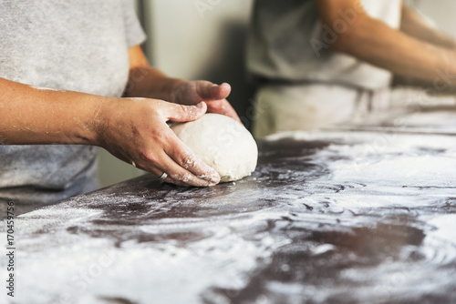 Baker preparing bread. Close up of hands kneading dough.