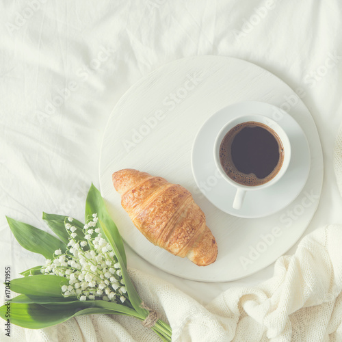 Fotobehang Lelietjes van dalen breakfast in bed. croissant, cup of coffee and Lily of the valley