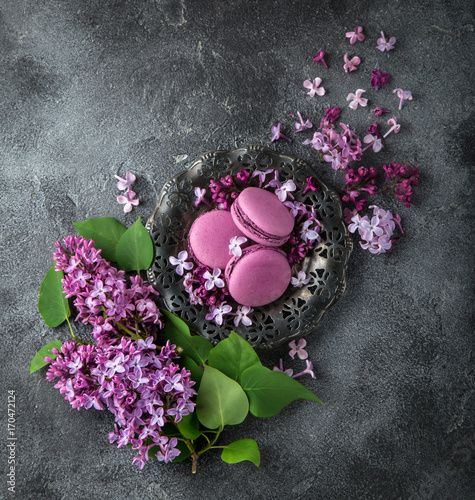 Fotobehang Macarons blackberry macarons on vintage plate and lilac flowers over grey texture background