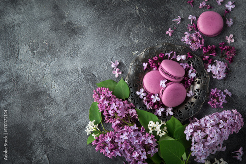 Fotobehang Macarons beautiful lilac flowers and blackberry macarons on vintage plate over grey texture background