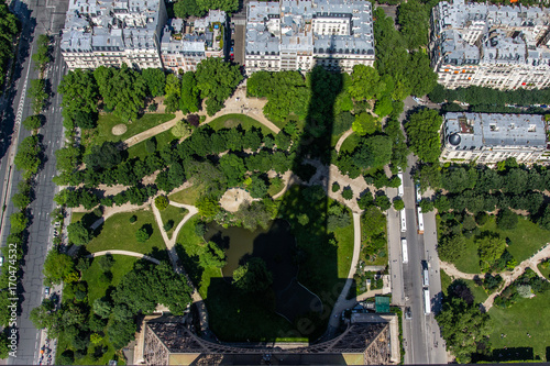 Foto op Aluminium Eiffeltoren the Eiffel tower's shadow over the nearby garden and pond and homes