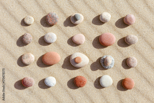 Foto op Aluminium Stenen in het Zand Pattern of colored pebbles on clean sand. Flat lay, top view