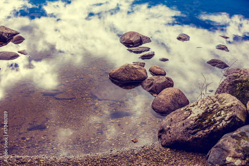 Stones in a water, sky reflection on the lake