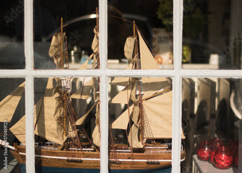 Keuken foto achterwand Schip Beautiful old model of sailing ship is visible behind a glass windows inside a room. A brigantine could be inside house, or decor of restaurant, shop, club, office. Symbol of good wishes - bon voyage!