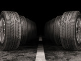 Car tires standing on the road on black background. - 170489309