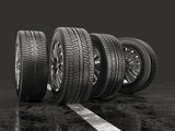 Four car tires rolling on a road on a gray background. - 170489384