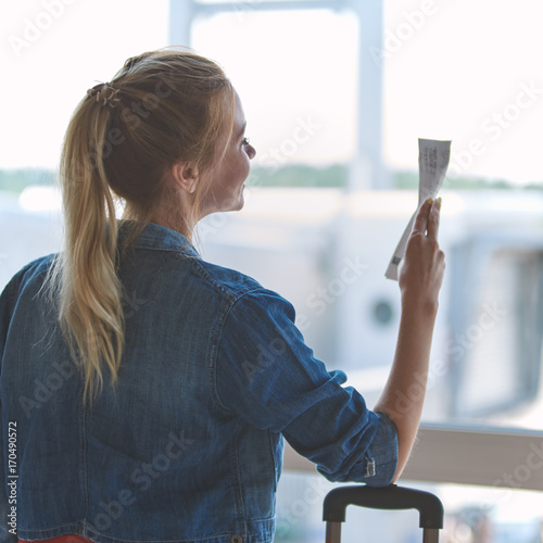 Young beautiful girl looking into the window while waiting for the boarding time in the airport.