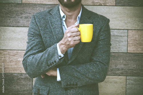 Poster businessman hand holding morning coffee at wall background