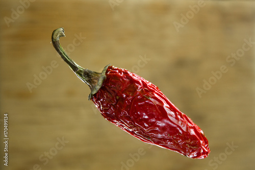 Foto Murales Stylish photo of a Red chili pepper levitating on brown wooden background