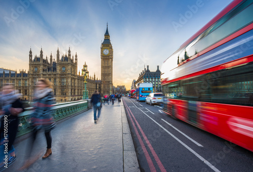 London, England - The iconic Big Ben and the Houses of Parliament with famous red double-decker bus and tourists on the move on Westminster bridge at sunset