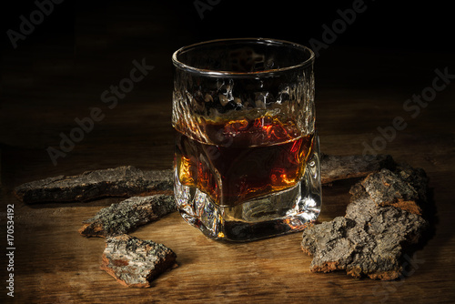 Whisky in the glass on wooden table. Brutal vintage concept