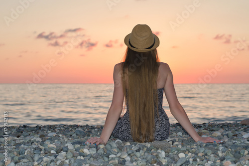 Foto op Canvas Zee zonsondergang Girl in the hat sitting on the seashore. Sunset time. View from the back