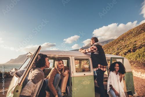 Friends on roadtrip relaxing by the van
