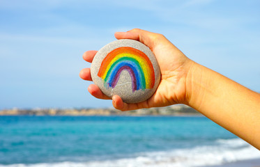 Woman hand holding pebble with painted rainbow