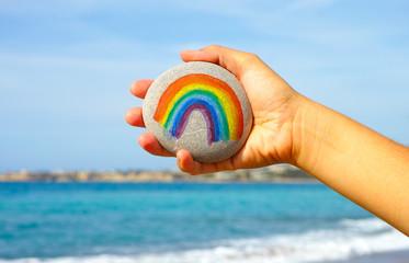 Woman hand holding pebble with painted rainbow © rosinka79