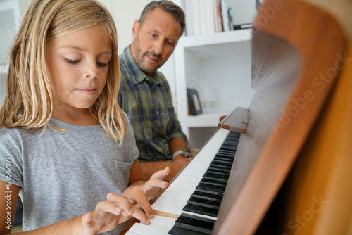 Fotobehang Muziek Little girl with teacher playing piano