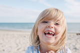 Blonde child with missing milk tooth laughing out loud - 170569150