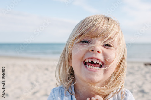 Blonde child with missing milk tooth laughing out loud