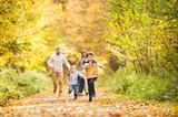 Beautiful young family on a walk in autumn forest. - 170573337