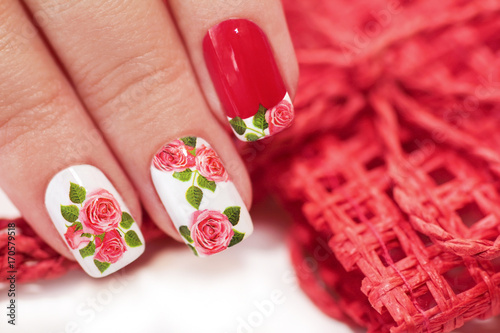 Fotobehang Manicure Red French manicure with a design of roses on a white background.