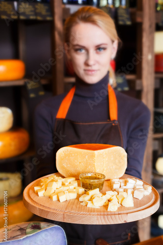 Poster Cheese platter in shop assistant hands