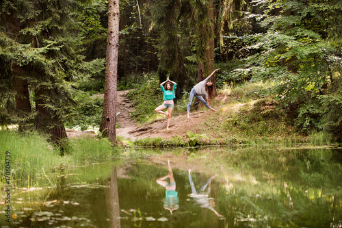 Obraz na płótnie Teenage girls practice yoga at the lake in forest.