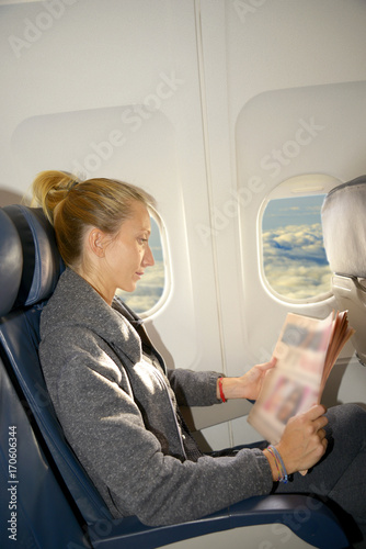 Woman reading newspaper in airplane Poster
