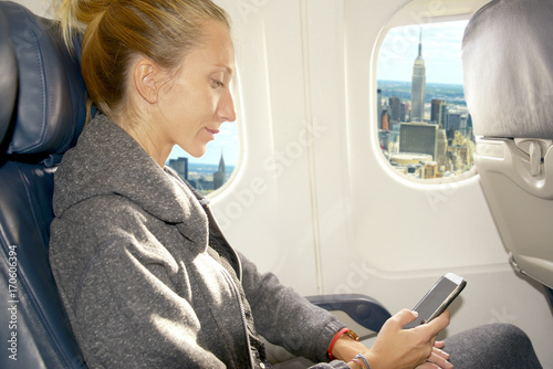 Woman messaging landing in New York city Poster