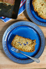 Cake. Lemon zucchini bread. Wooden table, blue plate, white background.
