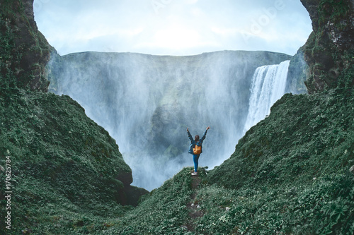 Girl in waterproof clothing stands on the cliff on background of Skogafoss waterfall in Iceland. back view, woman holds hands up