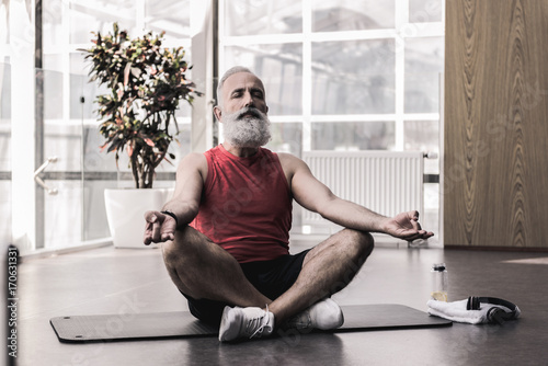 Fotobehang School de yoga Pleasant old man is enjoying yoga in fitness center