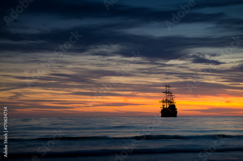 Fotobehang Zee zonsondergang Pirate ship in sunset scenery.