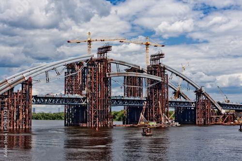 Fotobehang Kiev Combined car and subway bridge under construction. Mounting of steel arch. Unfinished Podolskyi bridge. Kiev, Ukraine. Kyiv, Ukraine.