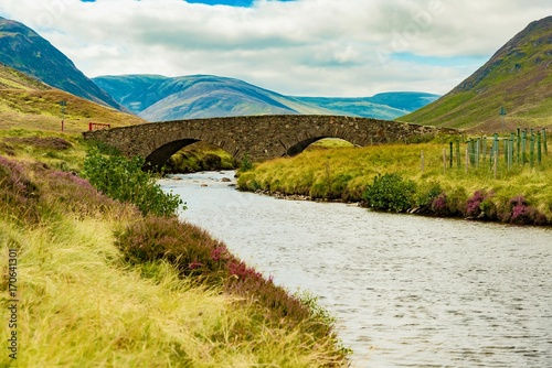 Papiers peints Miel panorama of small medieval stone bridge on the Highland in Scotland
