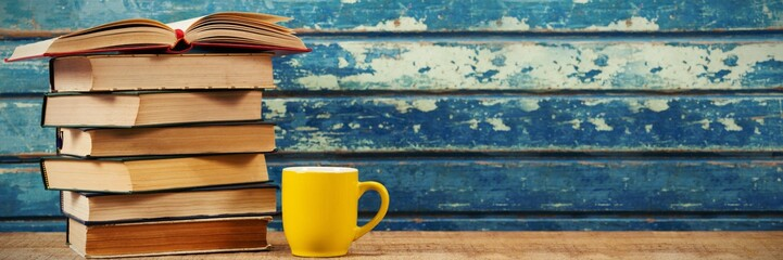 Stack of books with cup on table © vectorfusionart