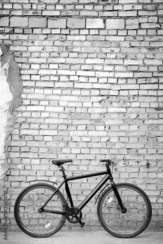 Aluminium Fiets Black bike against brick wall