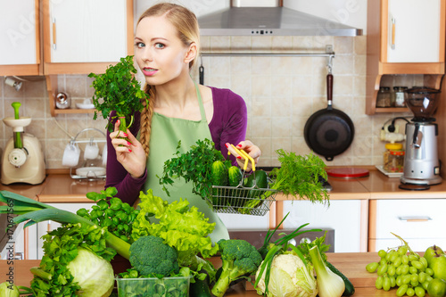 Woman in kitchen having vegetables holding shopping basket