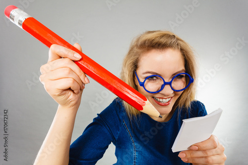 Crazy woman holds big pencil in hand