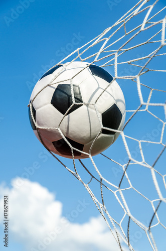 Soccer football in Goal net with the sky field. Poster